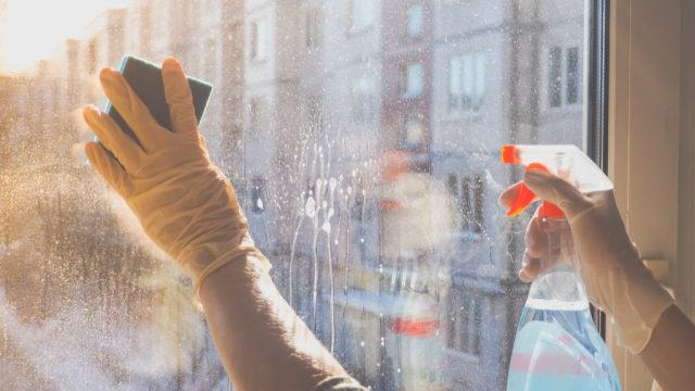 person cleaning a glass window, easy home tips