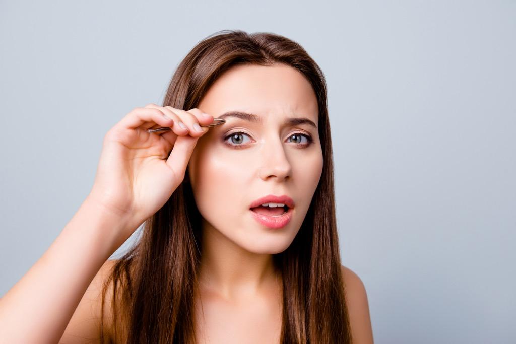 woman overplucking eyebrows