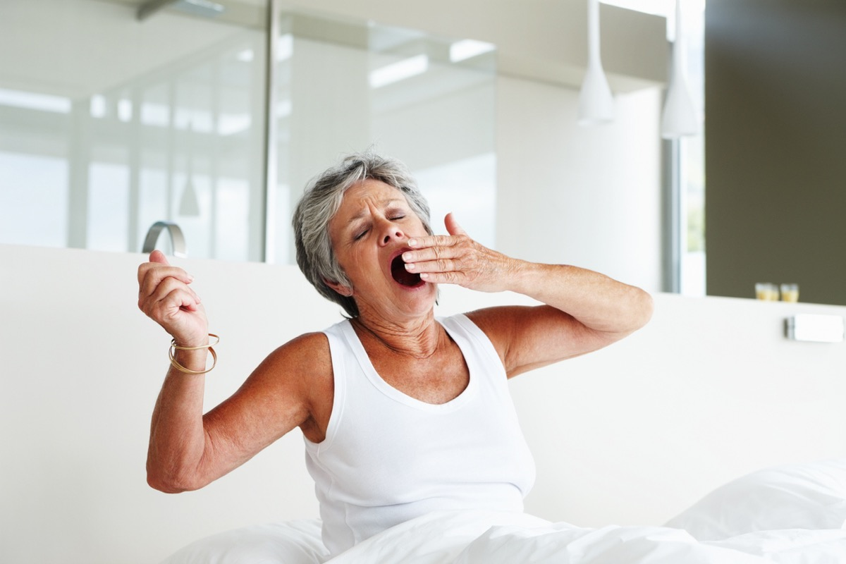 Senior woman sitting on bed and yawning with eyes closed