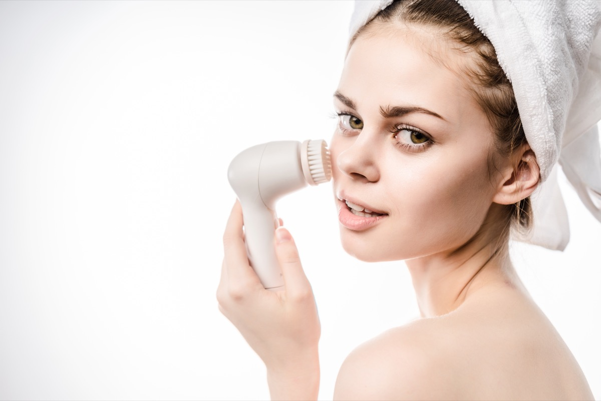 Woman using a skin cleaning brush tool