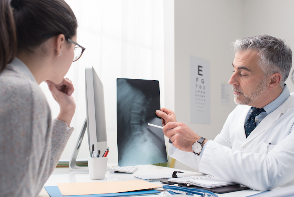 woman and doctor looking at an x ray of a spinal injury