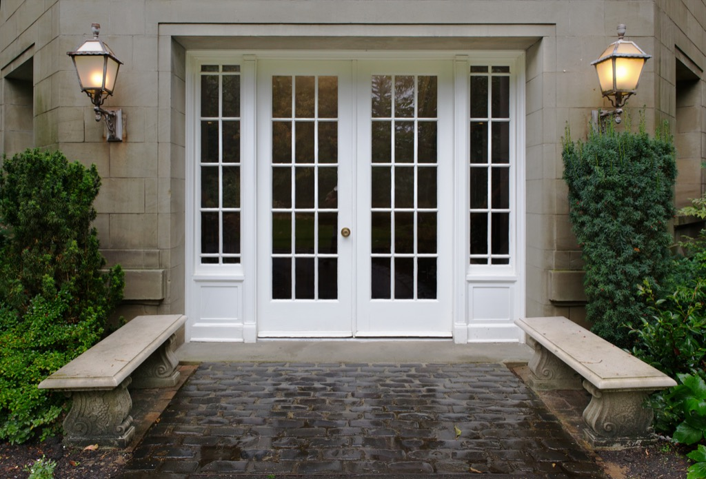 a stone walkway leading to french doors and brass sconces