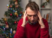 stressed man in red sweater holds head while sitting near christmas tree