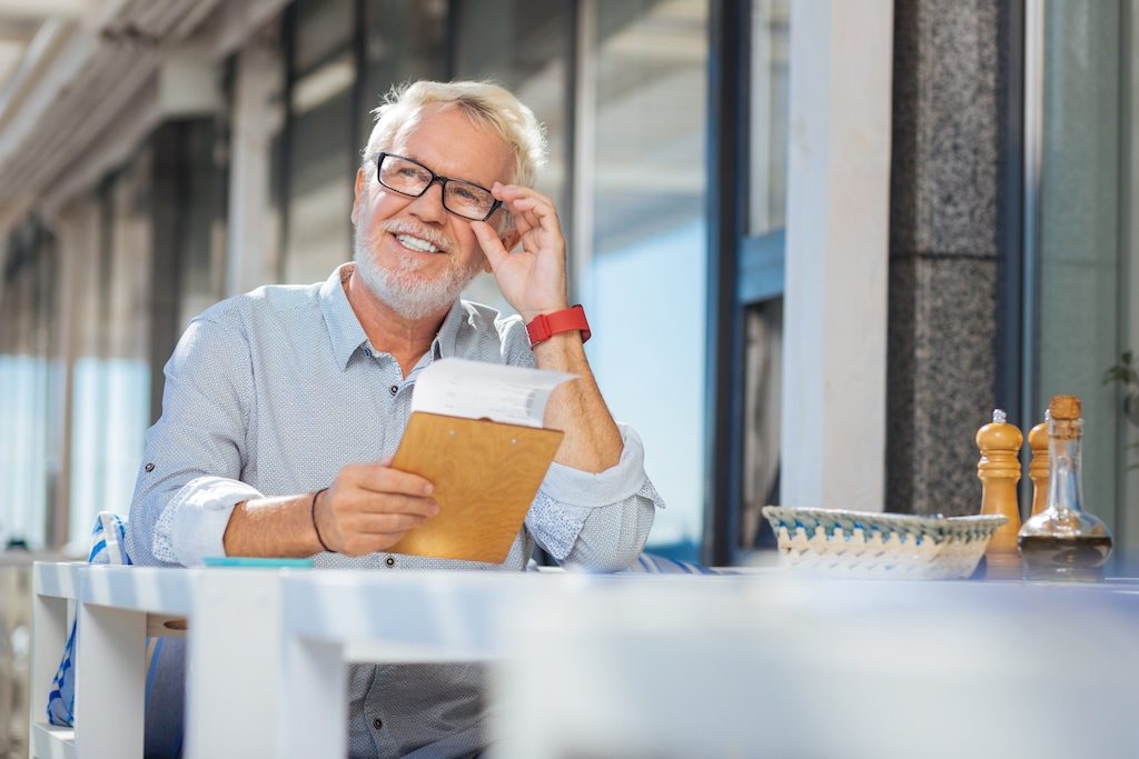 older man happily eating at a restaurant table by himself, single after 40