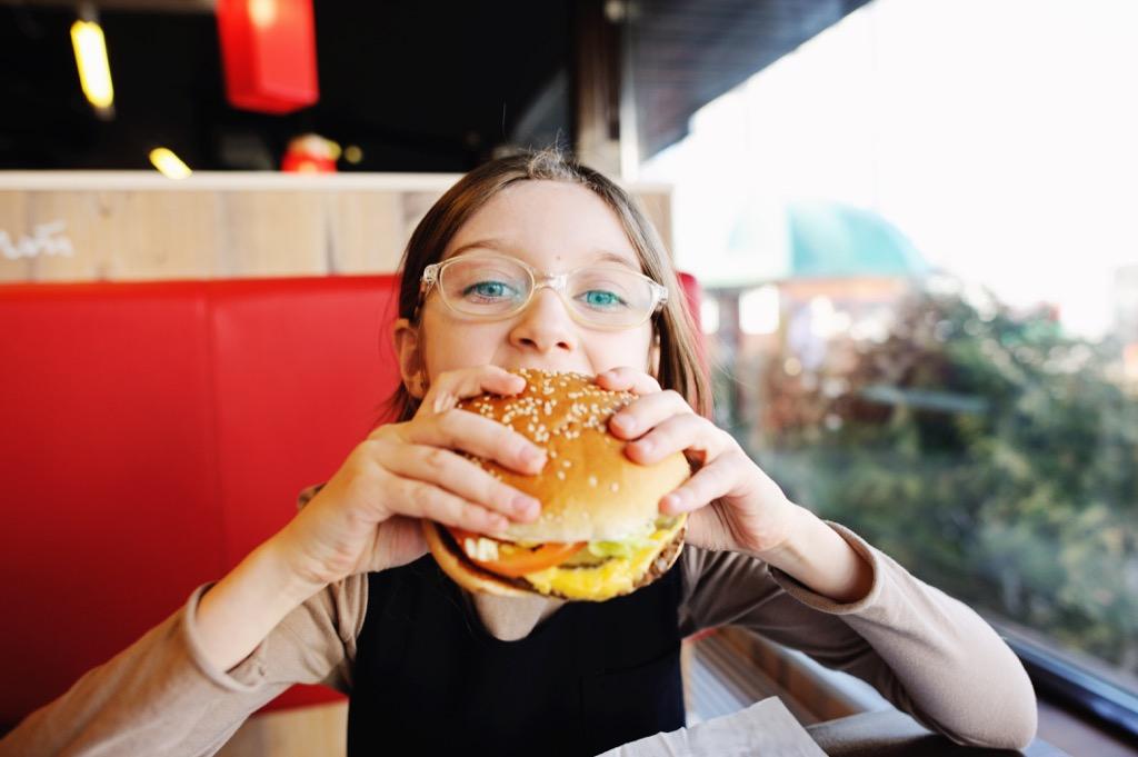 teen eating burger at restaurant