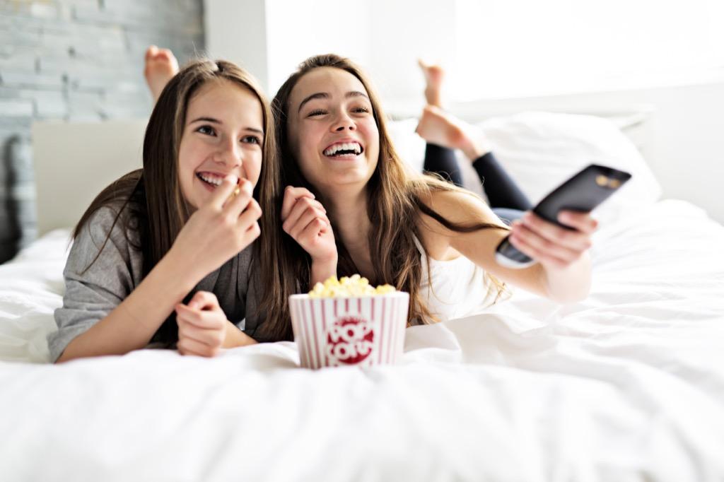 teens watching movie in bed