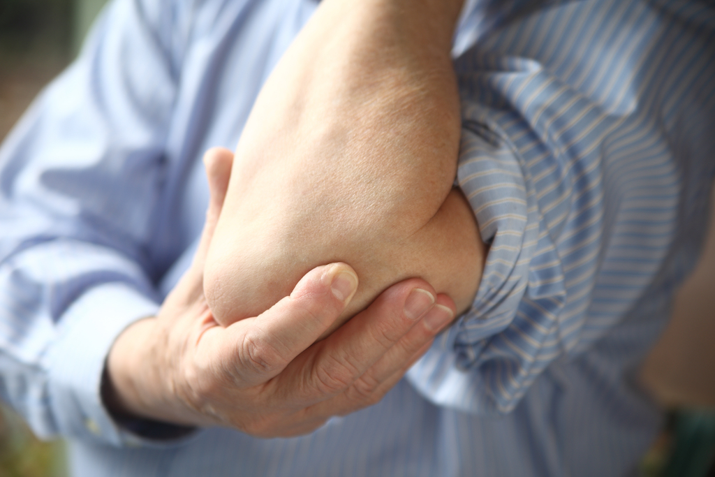 man holding his elbow because of tennis elbow pain men's health concerns over 40