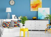 trendy home interior with white furniture and floors, yellow and blue art, blue wall with clock, and white lamp