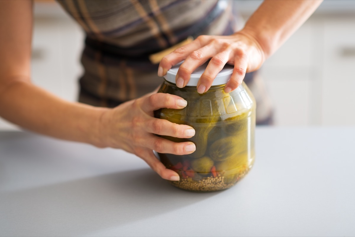 woman trying hard to open a jar of pickles