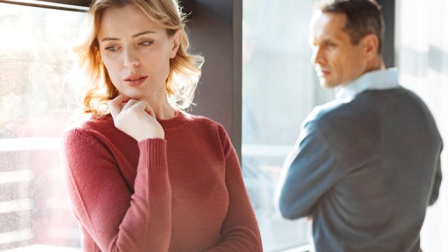 couple looking upset while standing near a window, taking a break in a relationship