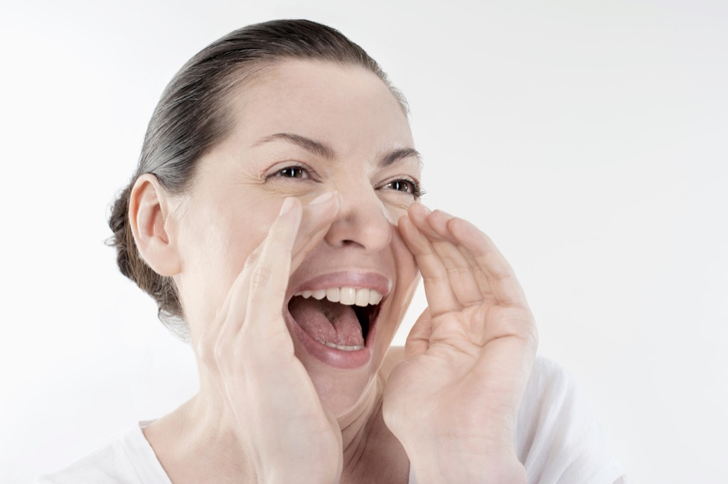 Mature woman shouting and screaming isolated over white background