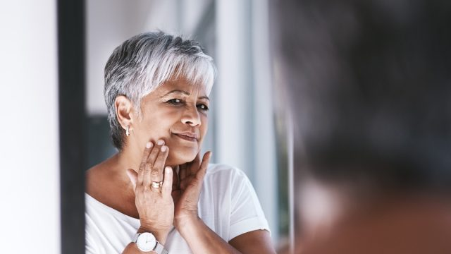 Mature woman touching her face with her hands while looking at her reflection in a mirror