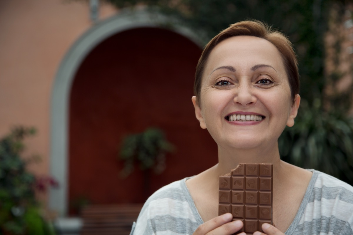 Older Woman Eating a Bar of Chocolate, smart person habits