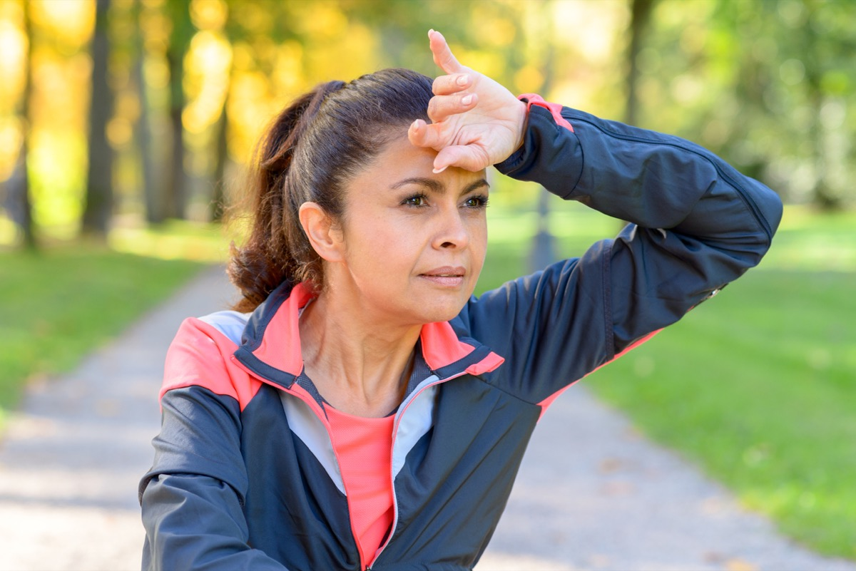 Woman wiping her brow with the back of her hand as she jogs outdoors in a park looking to the side with a thoughtful serious expression