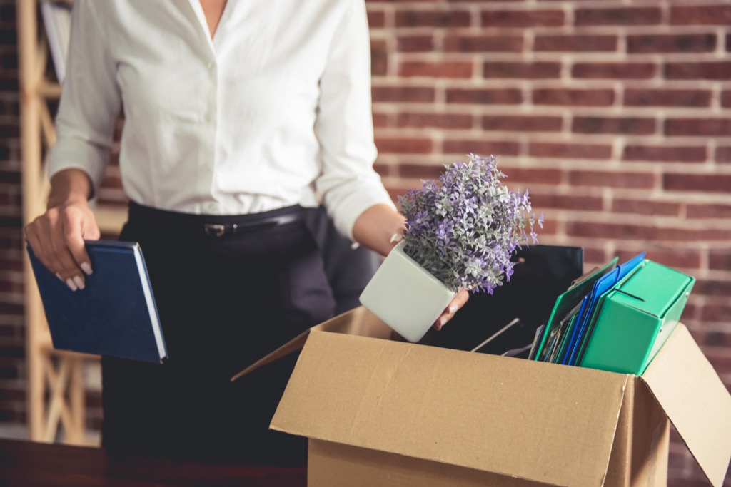 woman getting fired and putting her things in a box
