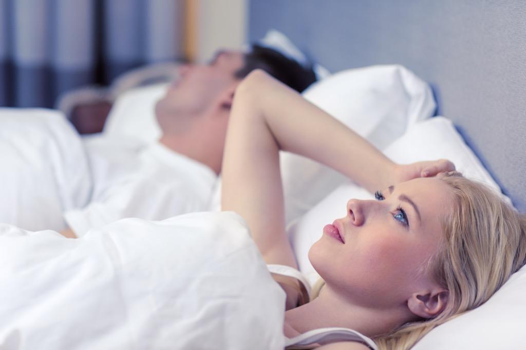 woman lying awake at night in bed with sleeping husband
