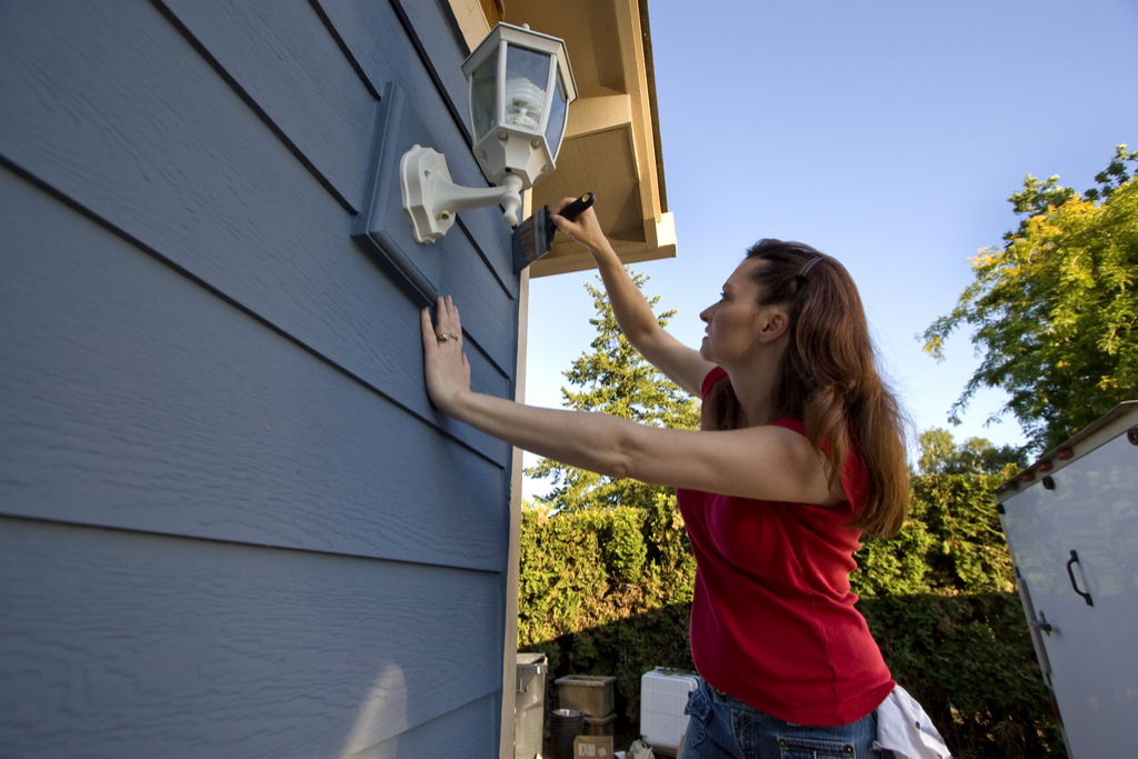 Woman Painting Outside of Home Boosting Your Home's Curb Appeal