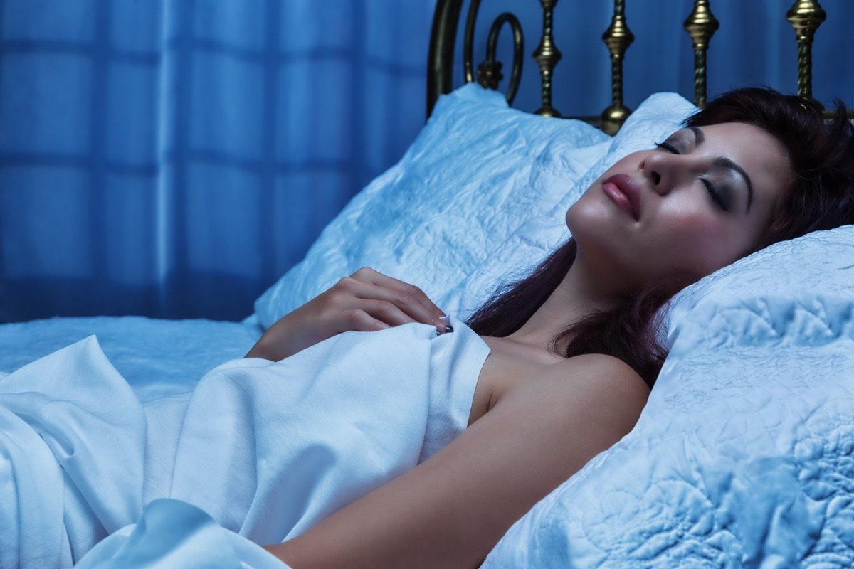 young woman sleeping with makeup on in bed
