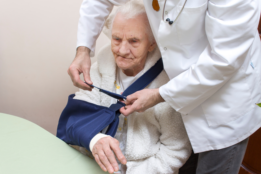 old woman getting a sling for her injury