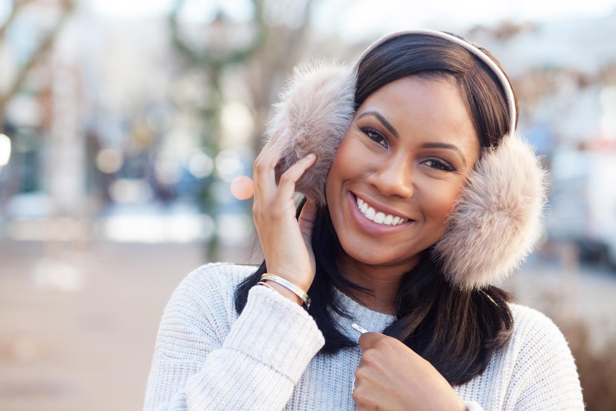 Woman in earmuffs smiling in the winter