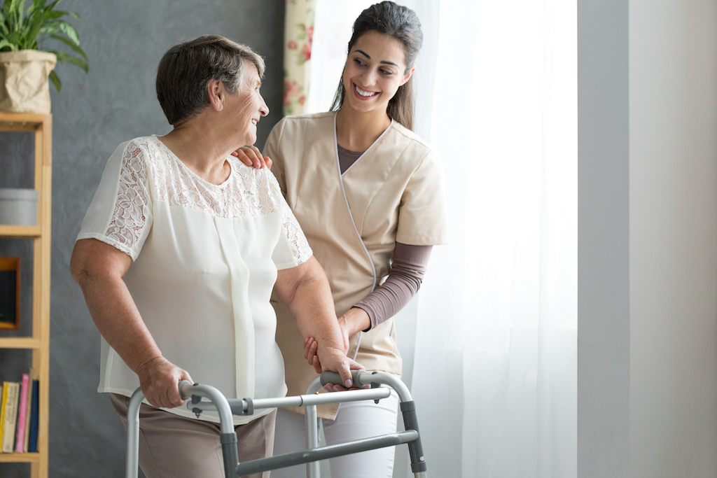 old woman using a walker as she recovers from hip surgery