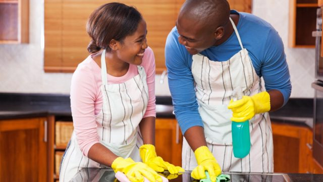 Young black couple cleaning house