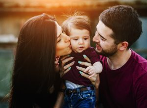 a young child being held by mom and dad, how parenting has changed