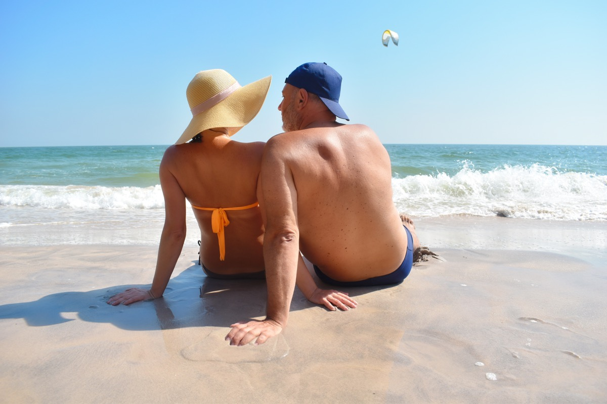 Older couple sitting in sand