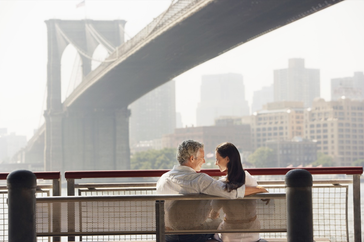 Couple sitting by bridge on a bench