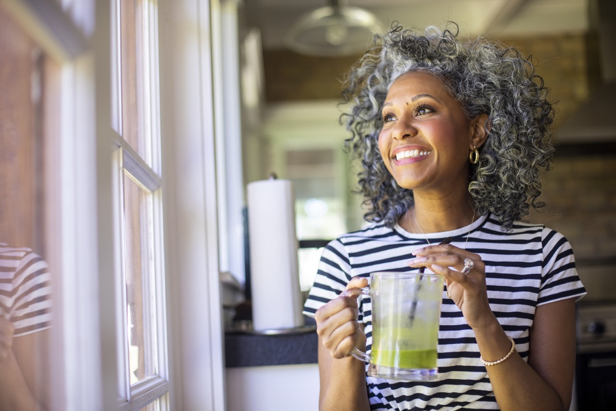 middle aged black woman with white curly hair drinks a green smoothie in the morning for breakfast