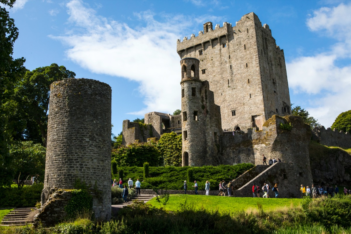 medieval castle in ireland with tourists on its lawn