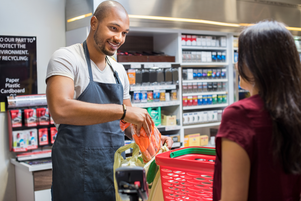 young black male cashier bags carrots for woman at grocery store