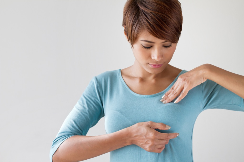 woman checking breast, subtle symptoms of serious disease
