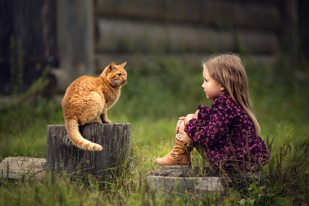 little girl is outside playing with her cat
