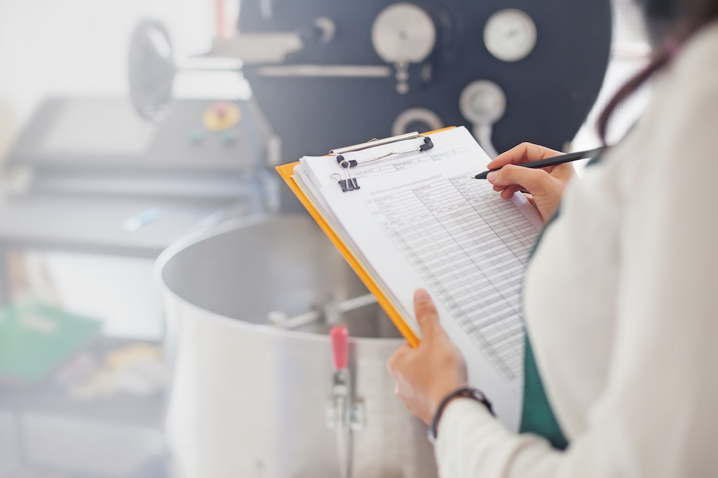 woman with a clipboard taking notes in a kitchen