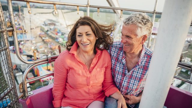 middle aged man and woman visit the fairground to enjoy the rides together