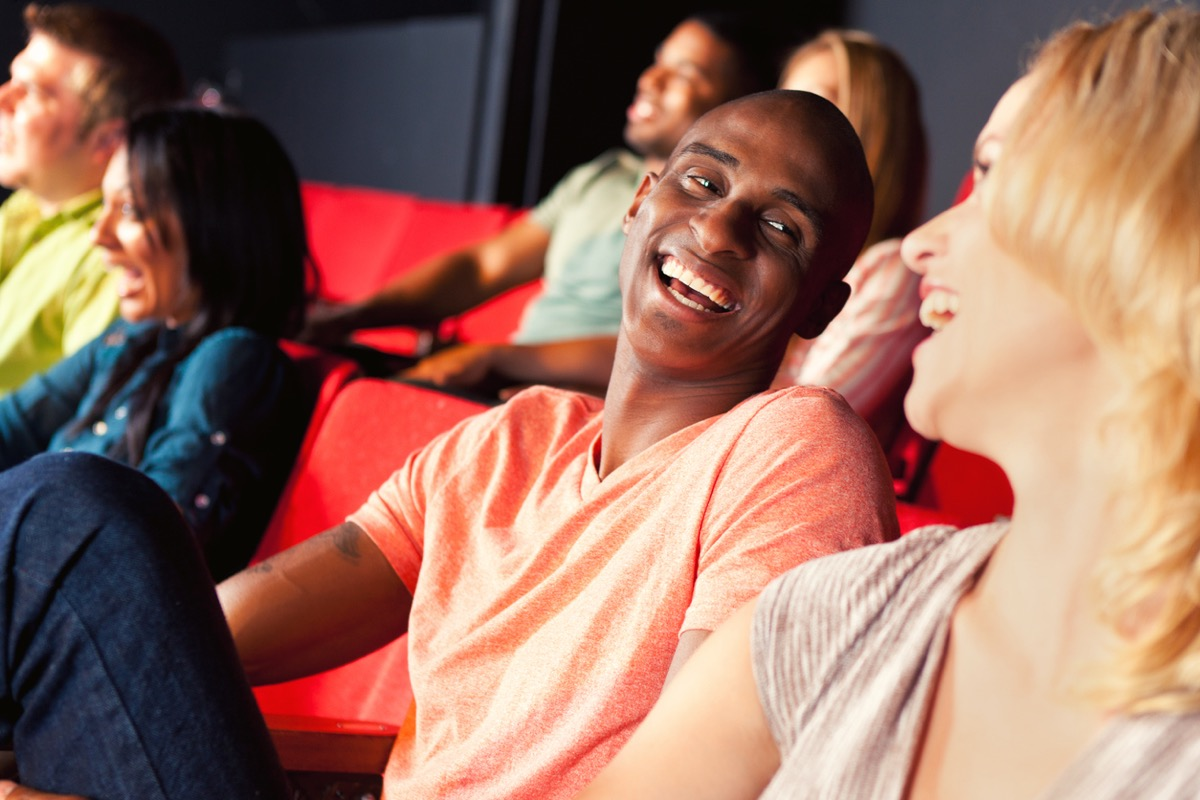 African American man smiles and laughs while watching a movie or show with his girlfriend
