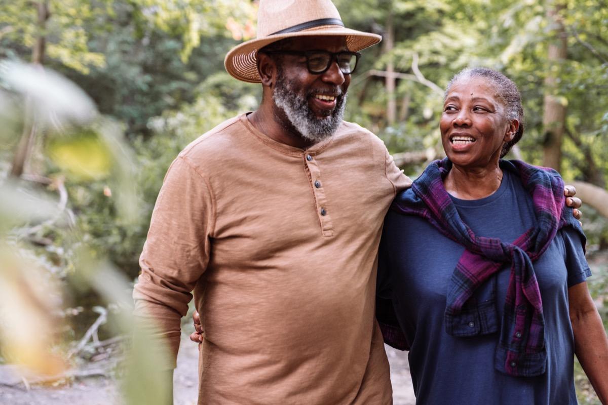 Smiling senior couple walking in a garden