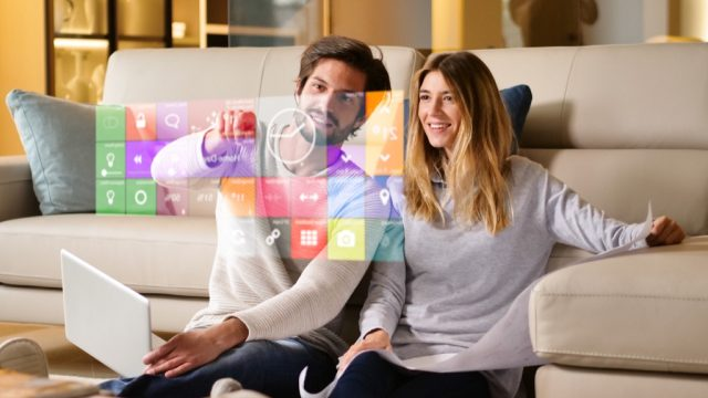 couple sitting on a sofa playing with augmented reality smart home settings