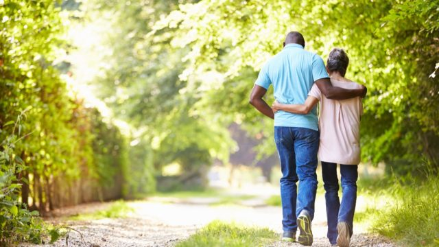 couple walking down a sunny wooded path