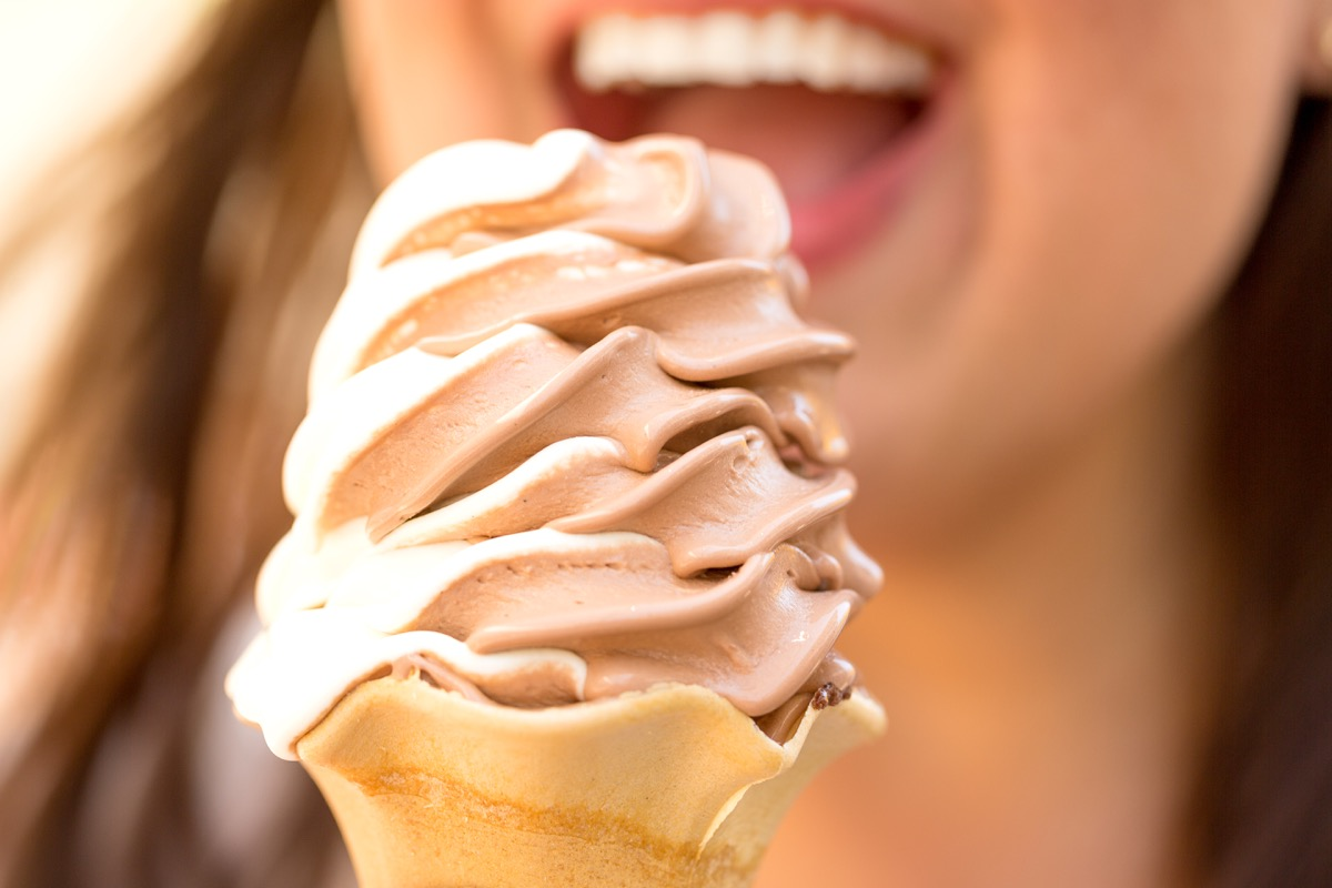 Woman eating chocolate and vanilla ice cream on a cone
