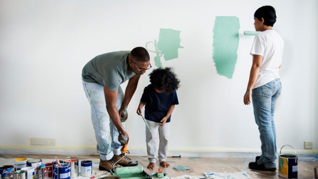 family painting a living room wall