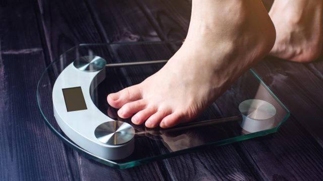 woman stepping on scale, healthy sex after 40