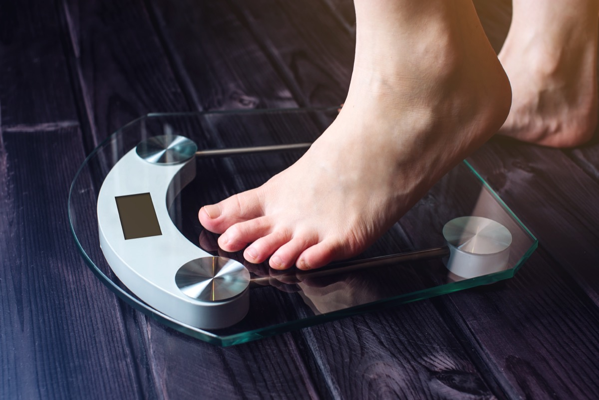 a person stepping on an electronic scale - terrible weight loss tips