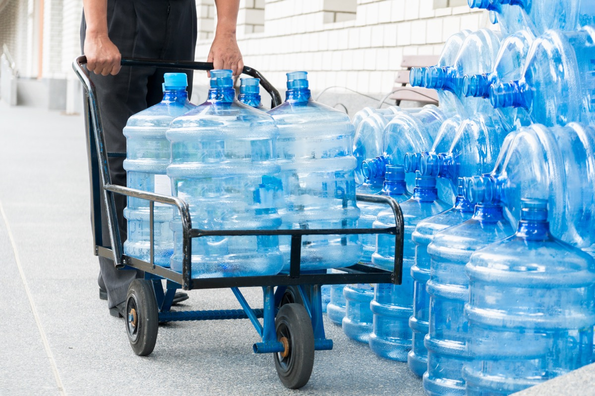 Man pushing a cart full of gallons of water
