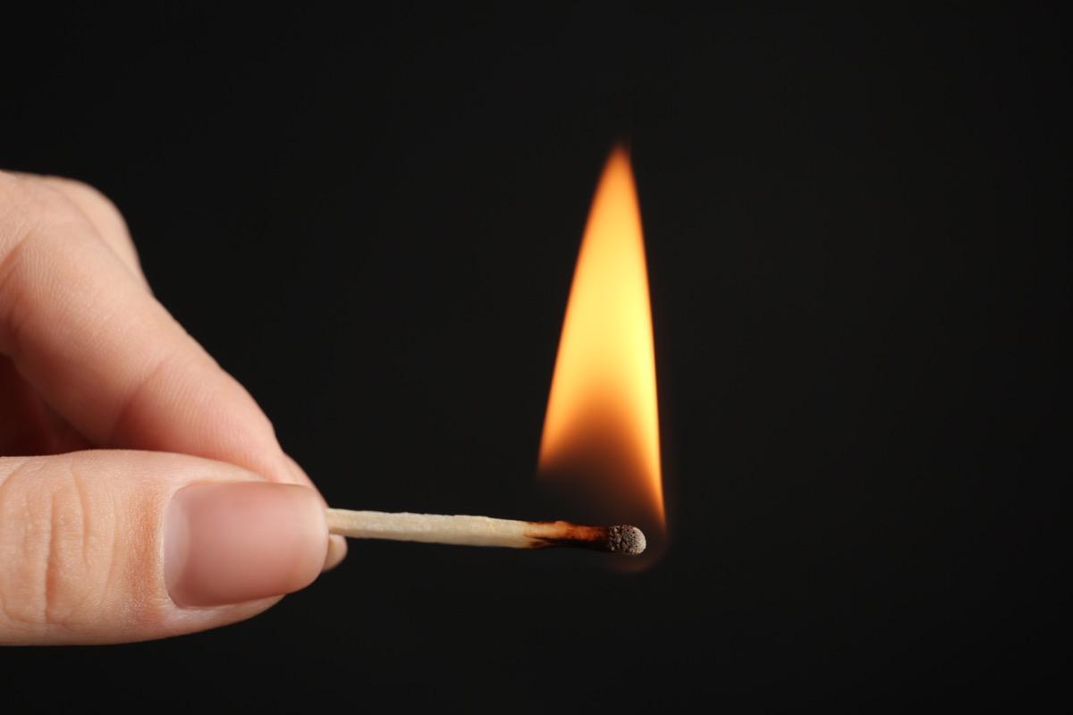 Hand holding a lit match