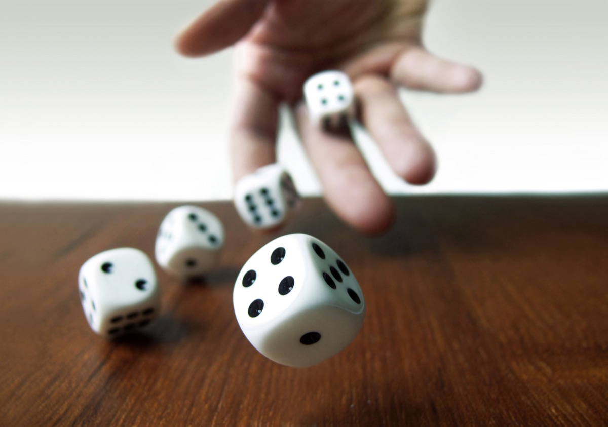 Hand throwing rolling dice