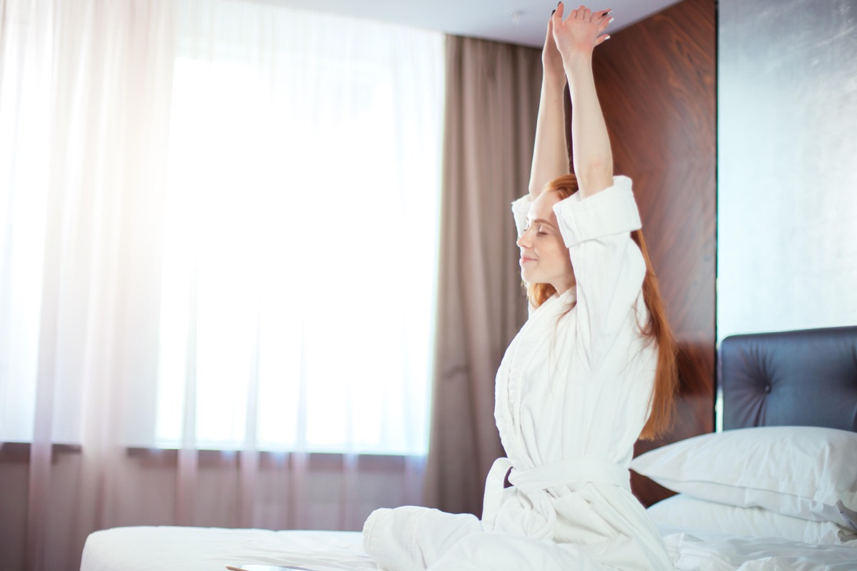 Happy woman in bed who loves Daylight Saving Time
