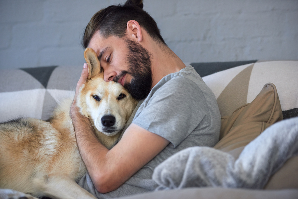 man in bed hugging his dog