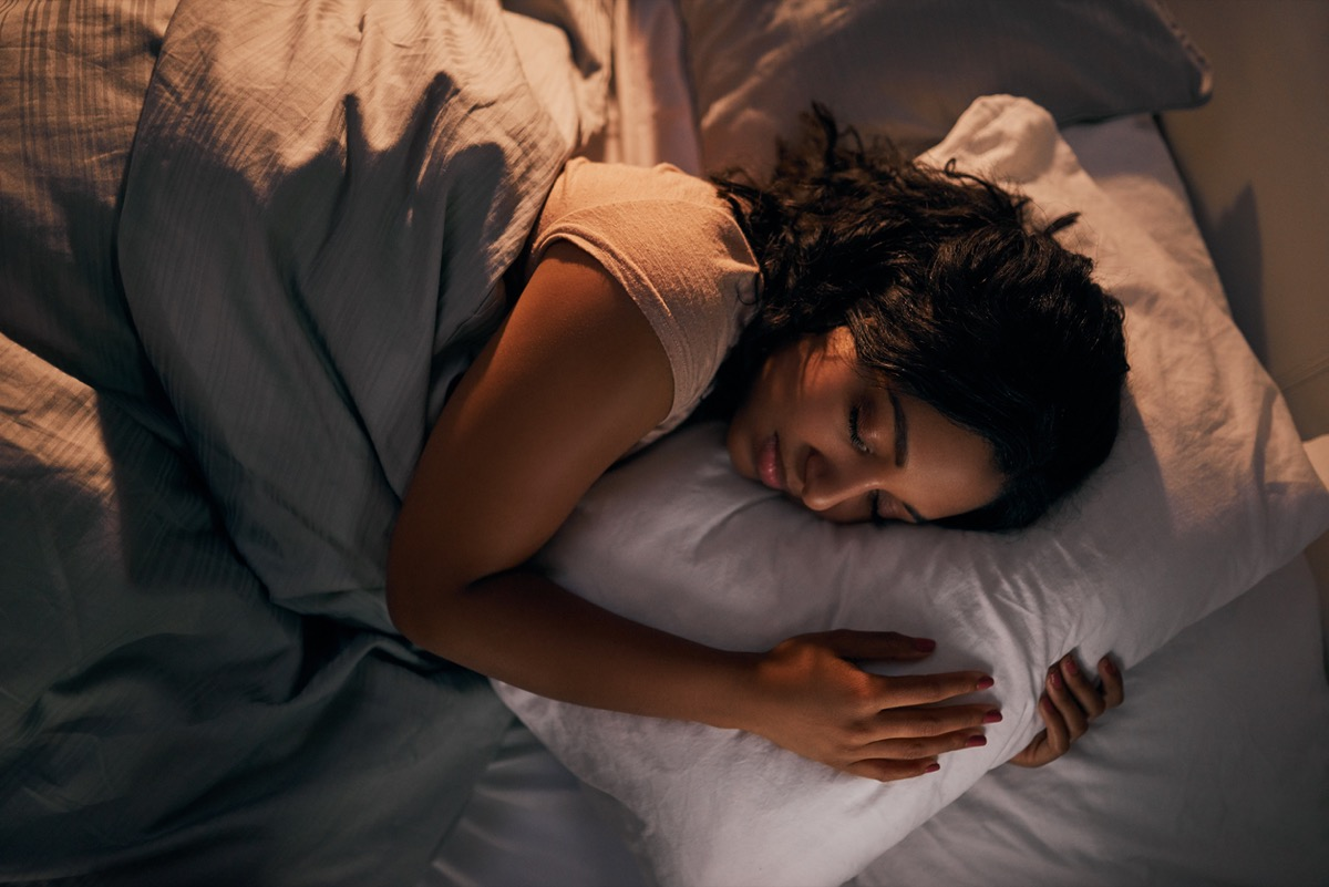 young woman sleeping while holding a pillow in bed
